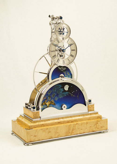 The Sun and Moon Clock, from Bob Bray FBHI (Sinclair Harding Clocks), features a panoramic changing sky as in real life, sunshine and clouds during daylight hours and the moon rising and setting every night. A special feature is that over twenty nine and a half days the moon goes through its phase, waxing and waning in the most realistic manner. The whole clock sits on a highly figured walnut, rosewood or black French polished base and the movement can be finished in either rhodium or gold.